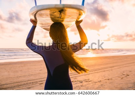 Surf girl with long hair go to surfing. Woman with surfboard on a beach at sunset or sunrise. Surfer and ocean #642600667