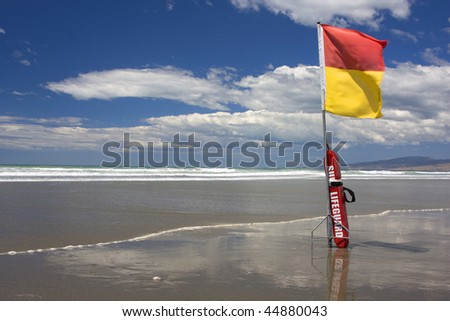 Surf Lifesaving flag and buoyancy aid on a New Zealand Beach