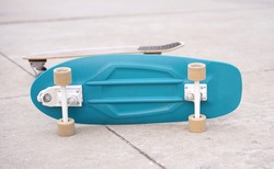Surf Skate, extreme sport with four wheels on board sliding on street or pump track. Famous teenager sport in urban. Blue board lays on ground with yellow wheels