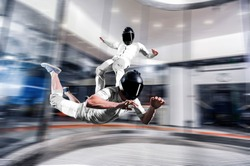 Surf sky . Men surfing on back of his friend. Indoor skydiving skysurfing. Free fall in wind tunnel.