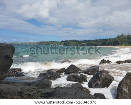 Surf spray and Sea foam. Kapalua beach. Wave action at Kapalua beach. Foam and surf spray. Sandy beach and large rocks. Barriers. #528046876