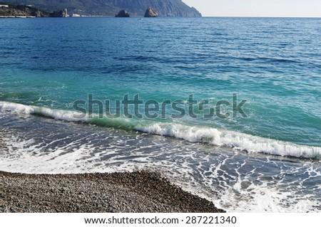 Surf, view of foot of Bear mountain( Ayu-Dag) and rocks-twins Adalari, Gurzuf, Crimea.