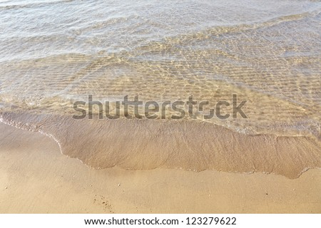 Surf wave is covering a sea beach sand