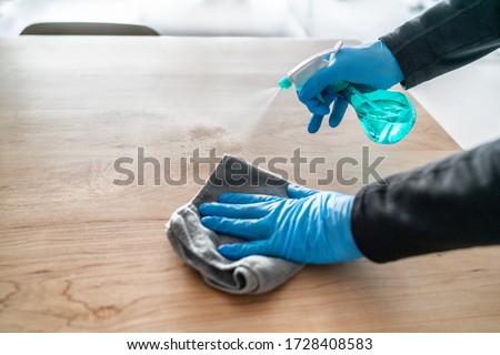 Surface cleaning spraying antibacterial sanitizing liquid with bottle washing table top at home . Man using gloves and towel doing spring cleaning.