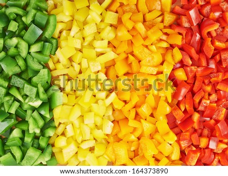 Surface coated with a sweet bell pepper cut into colorful pieces composition as an abstract food background