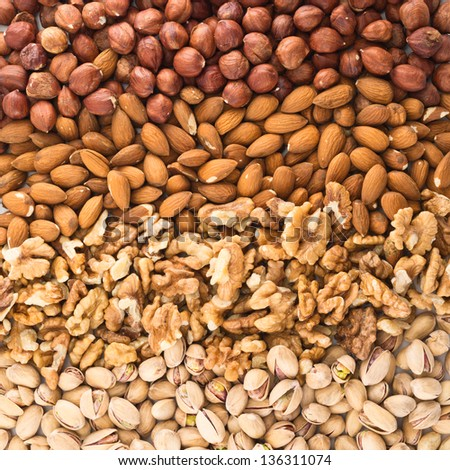 Surface covered with different nut mix of hazelnut, pistachio, almond, walnut as a food background