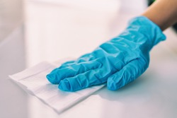 Surface disinfecting home cleaning with sanitizing antibacterial wipes protection against COVID-19 spreading wearing medical blue gloves. Sanitize surfaces prevention in hospitals and public spaces.
