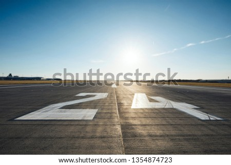 Surface level of airport runway with road marking and number 24 against clear sky.