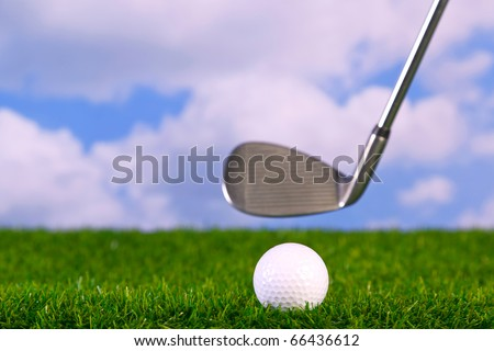 Surface level photo of an iron golf club in mid swing about to hit a ball on the fairway.