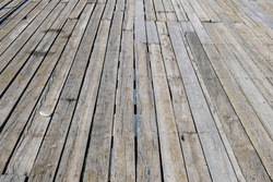 Surface of a wooden pier made of faded planks with cracks, gaps and crevices above the blue water close up