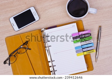surface of a wooden table with notebook, smartphone, eye glasses, and pen, top view