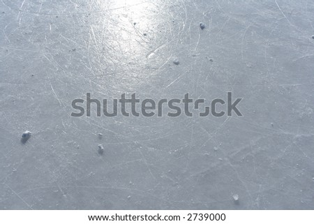 Surface of an outdoor ice rink replete with skate marks reflects the sun.