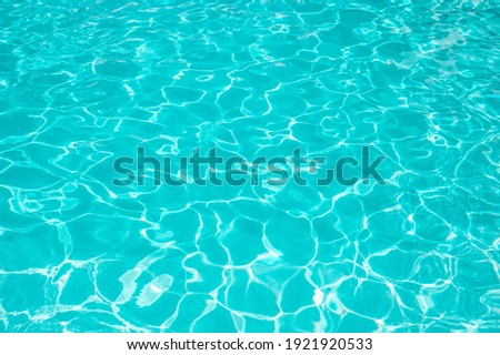 Surface of blue swimming pool. Summer background. Texture of water surface