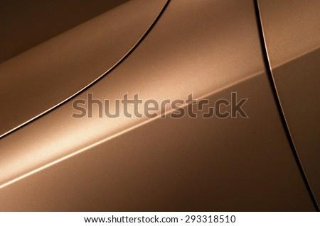 Surface of bronze sport sedan car, detail of metal hood, fender and door of vehicle bodywork