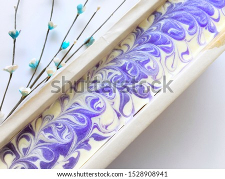 Surface of natural oil soap in wooden mold box and blue flower on white background, purple violet pattern, cold process, handmade product.