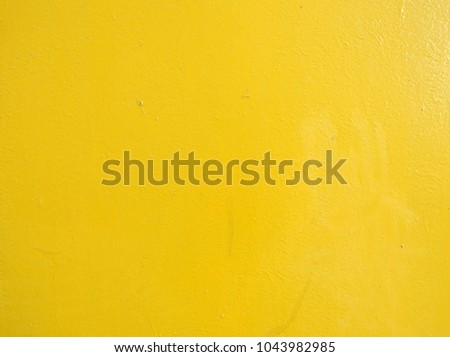 Surface of the wall, painted with bright yellow oil paint. Background texture.