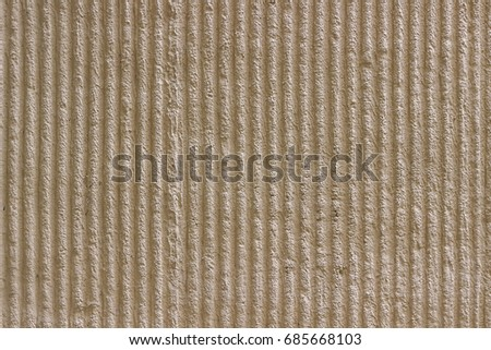 Surface of the wall with a decorative light beige plaster. Textured concrete wall with vertical lines and stripes as a texture or background. Repair, design concept.
