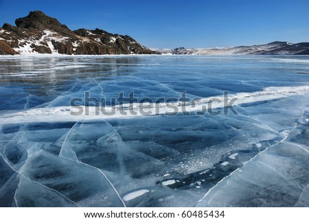 Surface of transparent fissured black ice of The Baikal Lake in winter