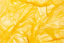 Surface of yellow wrinkled plastic bag. Texture of plastic film. Coating of polyethylene membrane. Abstract crumpled background.