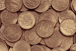 Surface or field of many Russian coins of 10 ten rubles. Dark brown yellow tinted background or wallpaper. Money, financial or banking backdrop for Russia. Top view from above. Macro