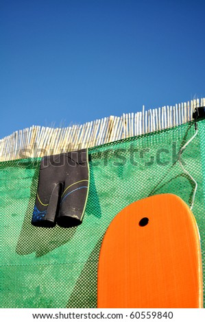 Surfboard and wetsuit on a fence at a beach - stock photo