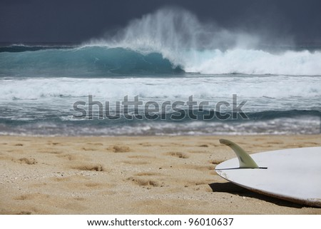Surfboard on a beach with waves in the background