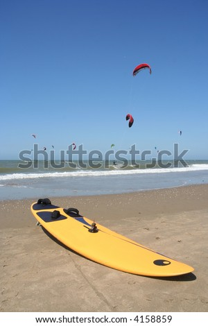 Surfboard on the beach with kite surfers