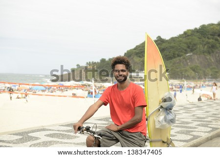 Surfer African descendant riding bicycle on the waterfront of Ipanema Beach in Rio de Janeiro. Brazil.
