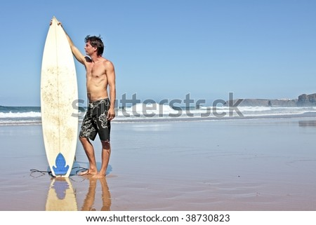 Surfer and his surfboard at the beach ready to surf