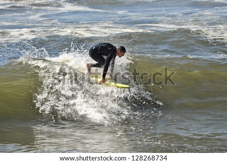 Surfer at the start of catching a wave in Oceanside, California.