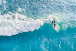Surfer at the top of the wave in the ocean, top view
