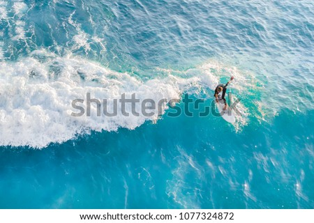 Surfer at the top of the wave in the ocean, top view #1077324872