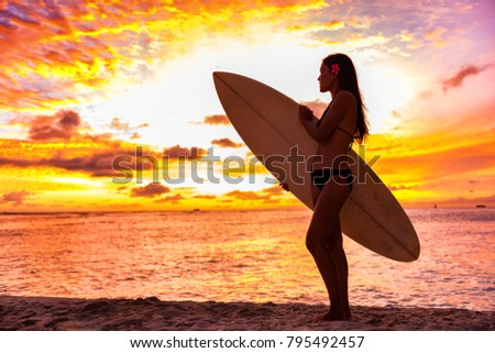 Surfer bikini girl on Hawaii beach holding surf board watching ocean waves at sunset. Silhouette of Asian sport woman over landscape, sky and clouds background. Summer vacation lifestyle.