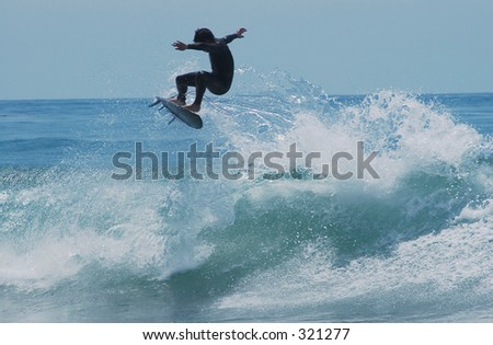 surfer catapulting out of wave getting air
