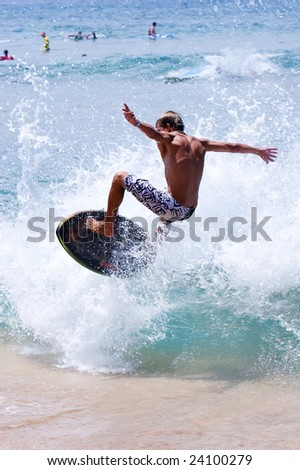Surfer catching waves with his skim board