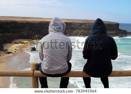 Surfer couple sitting on a fence wearing hoodies overlooking the waves hitting the beach and the cliffs