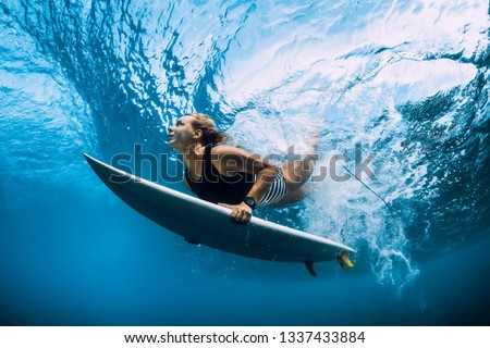 Surfer dive underwater. Surfgirl dive under big wave