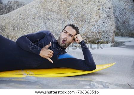 Surfer dude in wetsuit gesturing on board, portrait