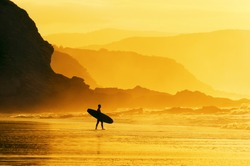 surfer entering water at the misty sunset