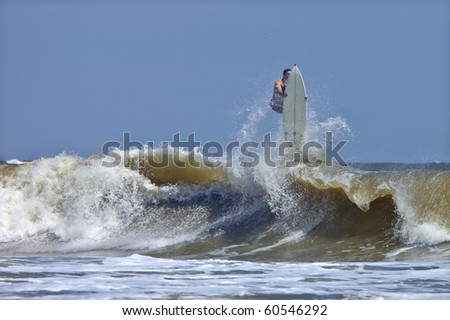 surfer getting big air and wiping out in rough atlantic surf