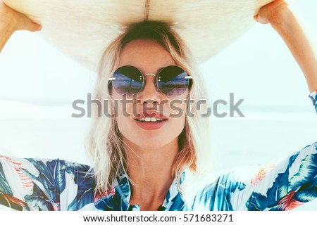 Surfer girl in sport swimwear and sunglasses posing with surfboard on the beach. Active lifestyle and summer vacations.