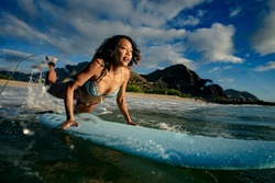 Surfer girl jumping into the ocean water right on a surfboard. Hawaiian sunset landscape on a background