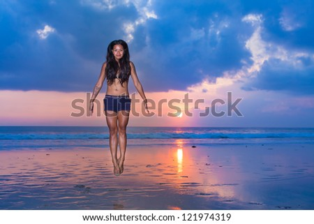 surfer girl levitating on the beach