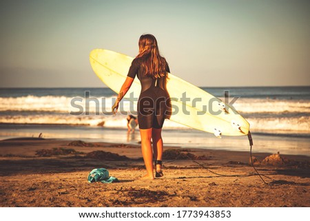 Surfer girl on a beach. Woman on a beach going to surf, carrying surfboard.