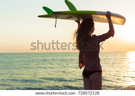 Stock Photo Surfer girl surfing looking at ocean beach sunset