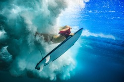 Surfer girl under wave against blue colored sea water surface