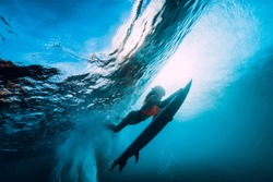 Surfer girl with surfboard dive underwater with fun under big ocean wave.