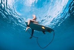 Surfer girl with surfboard relaxing at line up in ocean, underwater