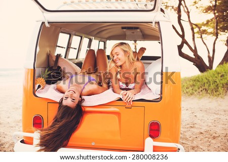 Surfer Girls Beach Lifestyle; Beautiful Surfer Girls Relaxing in the Back of Classic Vintage Surf Van on the Beach at Sunset