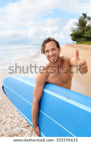 Surfer guy happy with surf surfing smiling doing thumbs up hand sign at camera after fun surf session in ocean waves on beach vacation. Surfing travel destination. Handsome sexy man topless. #503196631